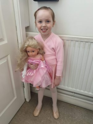 Emily in her Ballet uniform holding her dolly